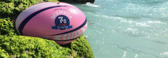 Rugby ball resting on a cliffside